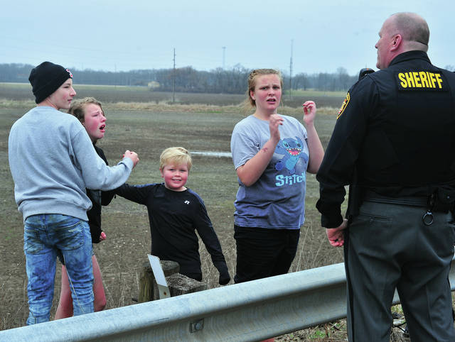 A group of juveniles speak to a Miami County Sheriff's Deputy after they created a few tense moments along the banks of the Great Miami River in Troy on Thursday.