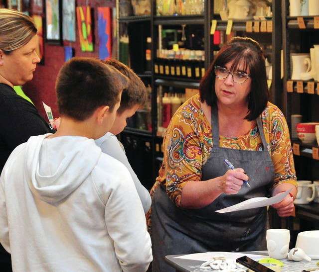Dawn Spoltman, owner and art instructor at Studio 14 Creative Arts Center in Troy, assists Dawn, Jaymes, Jaxson, and Jordan Carter in choosing crafts projects at the store last week.