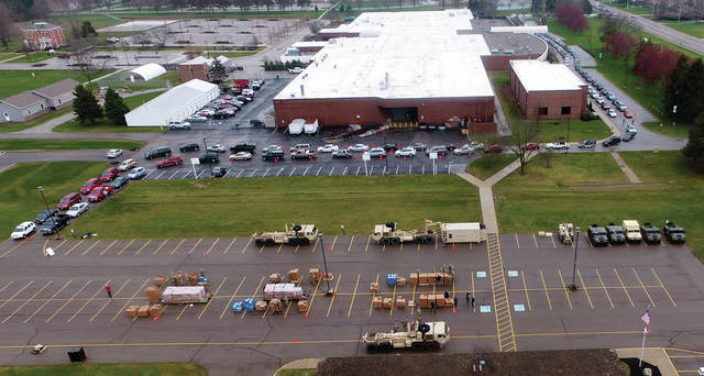 Hundreds of vehicles line up at the Upper Valley Career Center in Piqua, waiting for members of the Ohio National Guard to begin distributing food items from the Shared Harvest Food Bank on Saturday, March 28. The food is being distributed by members of Delta Company, 237th Brigade Support Battalion, Ohio National Guard. Delta Company is the forward support company the 2107th Cavalry Squadron, headquartered in Hamilton.