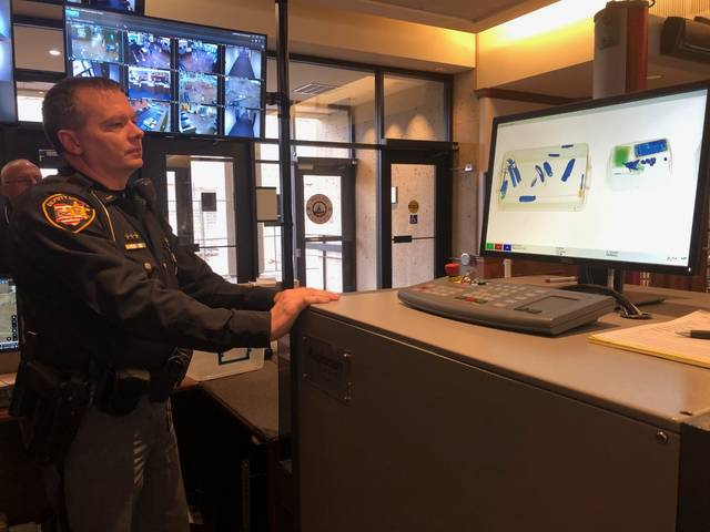 Deputy Richard Manns runs a tub full banned objects through the security system at the Miami County Safety Building. It was the first week the system was implemented.