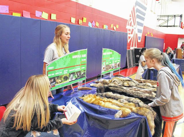 Link Crew members Ava Rowley, left, and Alysse Blain, center, both PHS juniors, interact with sixth-grader Autumn Arzola, right, during Monday's COSI on Wheels event at PCIS.