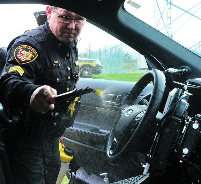 Miami County Sheriff's Office Sgt. Robert Morando sprays a disinfectant inside his cruiser on Thursday. The disinfectant and sprayer were donated to the sheriff's office by Midwest Commercial Services in Tipp City. The spray is safe for electronic equipment and dries quickly. All county cruisers will be disinfected regularly during the current COVID-19 crisis, thanks to the donation.