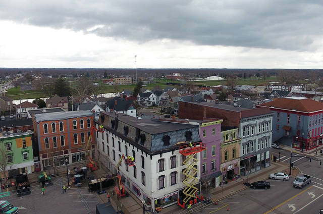 Rain clouds linger over downtown Troy on Wednesday as workers in forklifts, scissor lifts, and bucket trucks continue to repair damage done by the January tornadoes that hit Troy.