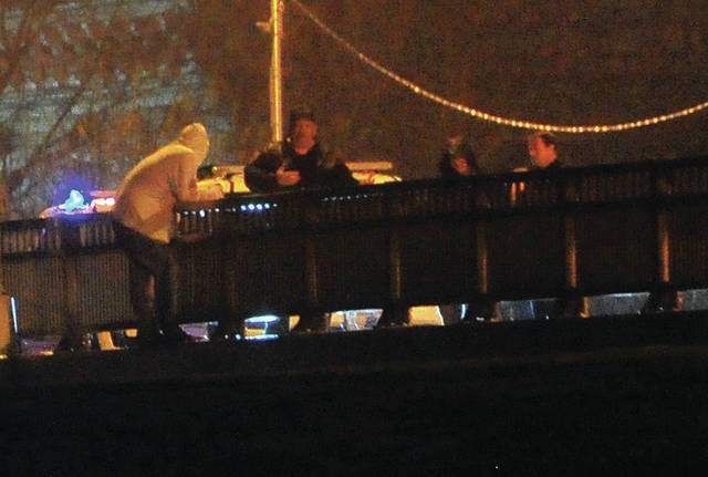 Troy Police officers talk with an apparent suicidal male on the North Market Street Bridge on Sunday night.