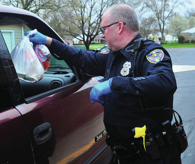 Troy Police Department SRO Tracy Long distributes lunches at Cookson Elementary School on Monday. One month in to the COVID-19 shutdown, Troy City Schools continues to provide approximately 7,500 meals every week for students.