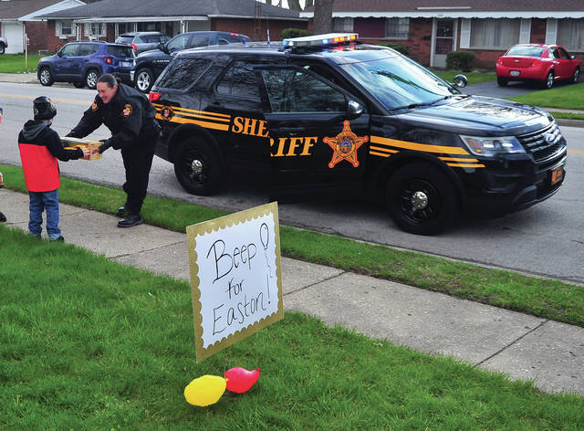 Deputy Sarah Fraley of the Miami County Sheriff's Office hands a gift to Easton Allman at his Piqua home earlier this week. Fraley, a family friend, along with an engine from the Piqua Fire Department and dozens of well-wishers drove by and honked horns to help celebrate Allman's sixth birthday.