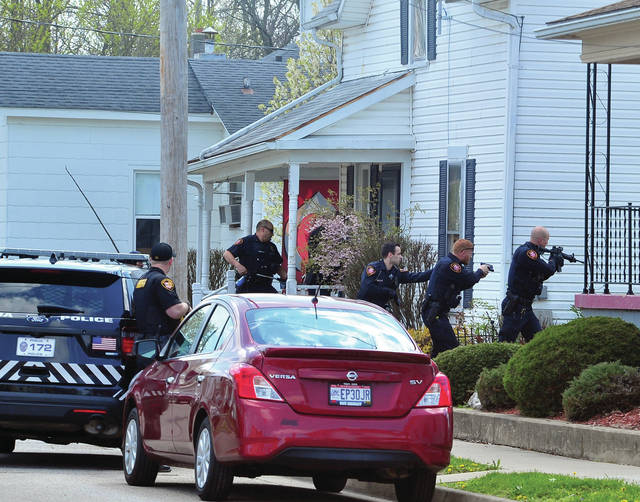 Piqua police officers prepare to clear a house on Walker Street on Thursday afternoon following a reported disturbance and shot fired.