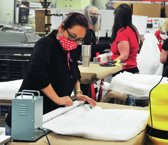 Rose Combs seals a protective gown at Industry Products Company (IPC) in Piqua on Friday morning. IPC is manufacturing gowns for Premier Health during the current COVID-19 crisis.