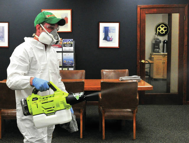 Tyson Dienstberger of CMC Management in Piqua uses a portable sprayer to sanitize and disinfect the Piqua Area Chamber of Commerce offices on Tuesday. As Ohio begins to reopen for business, owners and managers are taking steps to insure the health and safety of both employees and customers. The PACC will reopen beginning Monday, May 4, by appointment only.