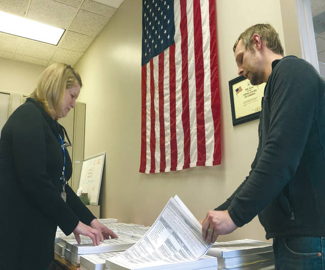 Left, Director Laura Bruns and Deputy Director Ian Ridgeway, sort absentee ballots at the board of elections office on Tuesday.