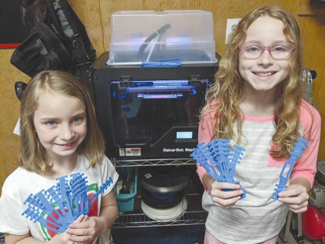From left, Eden, 7, and Willow, 10, have printed approximately 50 ear guards since Monday to donate to local healthcare workers. The guards help alleviate mask pain, moving the tight bands to the back of the head instead of the ear.