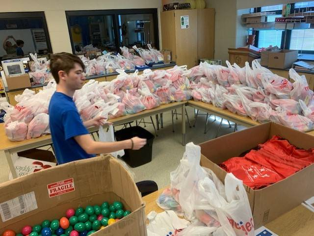 """Miami East High School junior Carter Gilbert, 17, filled and coordinated 333 dozen Easter eggs kits for local families last week. Gilbert had planned to host a community hunt, but adapted plans to make Easter Egg Hunt """"to-go"""" kits as part of his FFA passion project."""