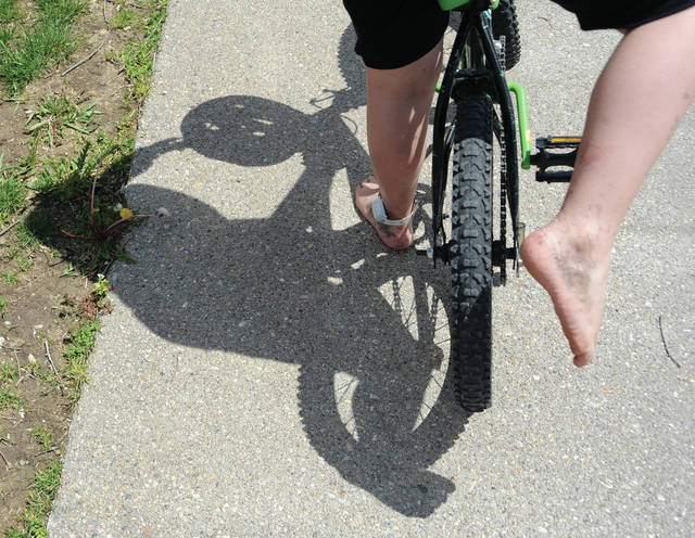 A six-year-old Troy youth straddles his bicycle at the Hobart Urban Nature Reserve on Friday as he, and law enforcement officials, wait for his mother to arrive after the boy left his home in the area of Morehead Street and Floral Avenue and rode his bike all the way to the Miami County Park District park on South Dorset Road before being located.