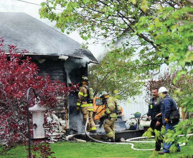 Firefighters from multiple departments work to extinguish a house fire on North Main Street in Casstown on Tuesday afternoon.
