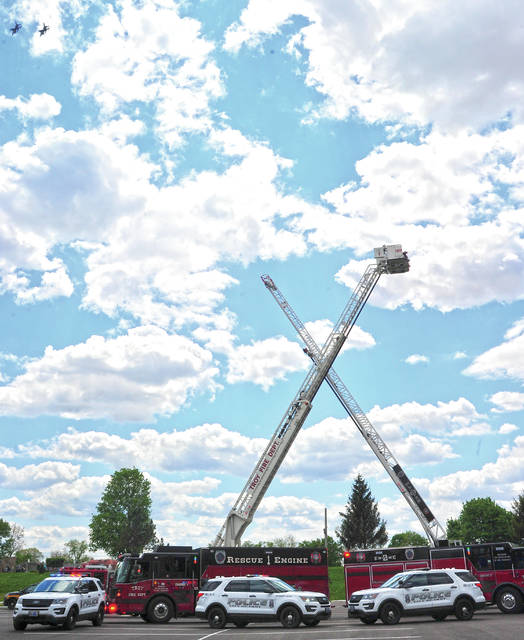 A pair of Ohio Air National Guard F-16 fighters, top left, make a pass over City of Troy First Responder vehicles at Hobart Arena on Thursday as the Ohio National Guard paid tribute to front-line EMS personnel across the state.