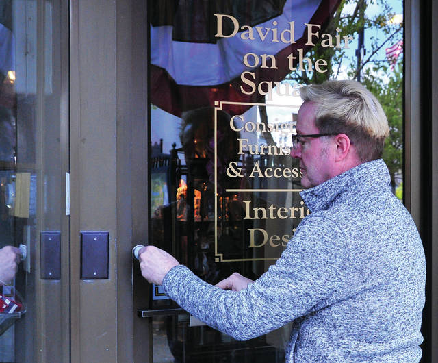 Long-time downtown Troy business owner David Fair unlocks the door to his David Fair on the Square shop on Tuesday morning as Ohio retail stores begin to again open for business amid the COVID-19 crisis.