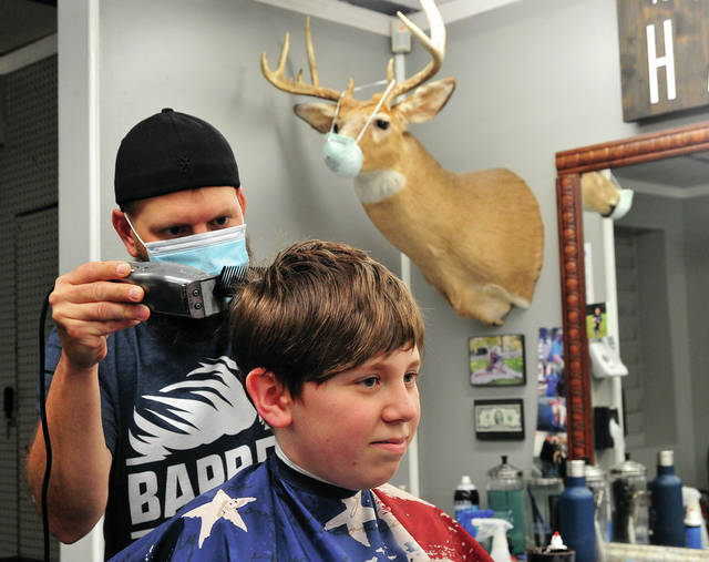 Jake Seger, 12, of Tipp City enjoys his first haircut in more than eight weeks as Chris Wenrick of Chris' Barber Shop in Piqua handles the trimmers. Friday was Wenrick's first day to be open for business since early March.