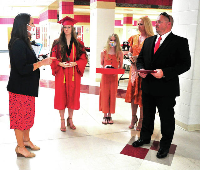 Tippecanoe senior Ashlyn England, along with her parents, and sister Mikayla, 11, receive instructions from Tippecanoe Assistant Principal Leslie Christofano before Ashlyn enters the gym to receive her diploma on Wednesday.