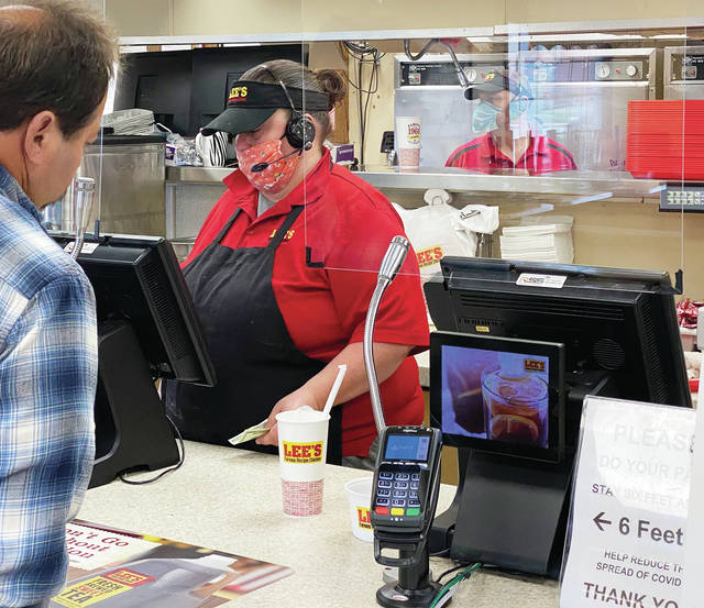 Crystal Smith takes a customer's order at the counter of Lee's Famous Recipe in Piqua on Thursday as indoor dining and service at restaurants opened to the public after a two-month shutdown.