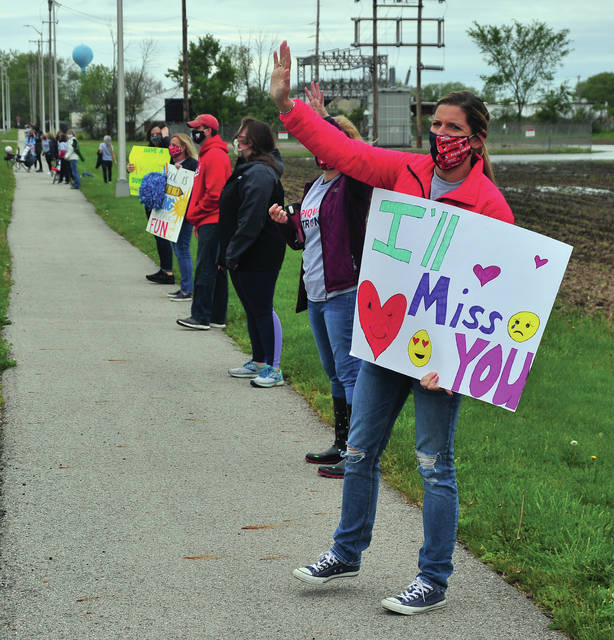 Washington Primary School third grade teacher Libby Leininger waves at some of her students during Thursday's Clap-Out event, held this year at Piqua High School.