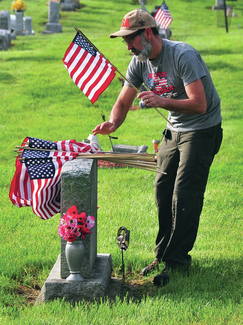 Todd Sonnanstine places a U.S. Flag on the grave of a veteran at Maple Hill Cemetery in Tipp City on Saturday morning. Sonnanstine, his son, Todd, and more than 20 other volunteers met to place flags on the graves of veterans for this Memorial Day weekend. Although barred, officially from doing their traditional placing of flags, Tipp City area scouts volunteered to help out with the project. Among those helping were Boy Scout Troops 395 and 586 out of Tipp City, Pack 395 from Tipp City, Troops 169 out of Huber Heights and Troop 94 from Bethel Township. Troop leaders explained that their participation was following their Charter and not an official duty.
