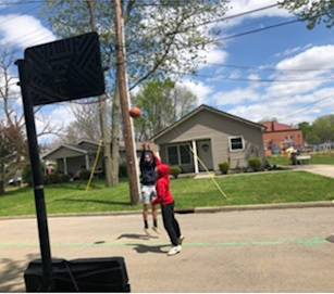 Kyreem 15, and Octavia Rambert, 16, play basketball at the dead end area of Cedar Drive. Several residents expressed their concerns with the Lincoln Community Center (in the background) plan to open the dead end as egress for emergency and maintenance vehicles and outgoing vehicles during their events.