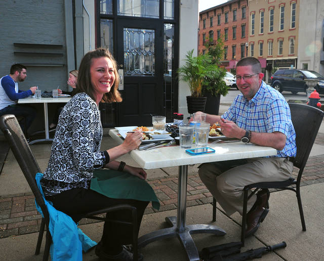 Diners enjoy a sidewalk dinner, the first in months, at the Caroline in downtown Troy on Friday evening