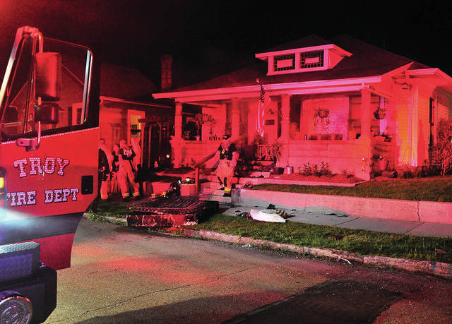 Troy firefighters work at the scene of a fire in the 800 block of South Clay St. on Friday evening.