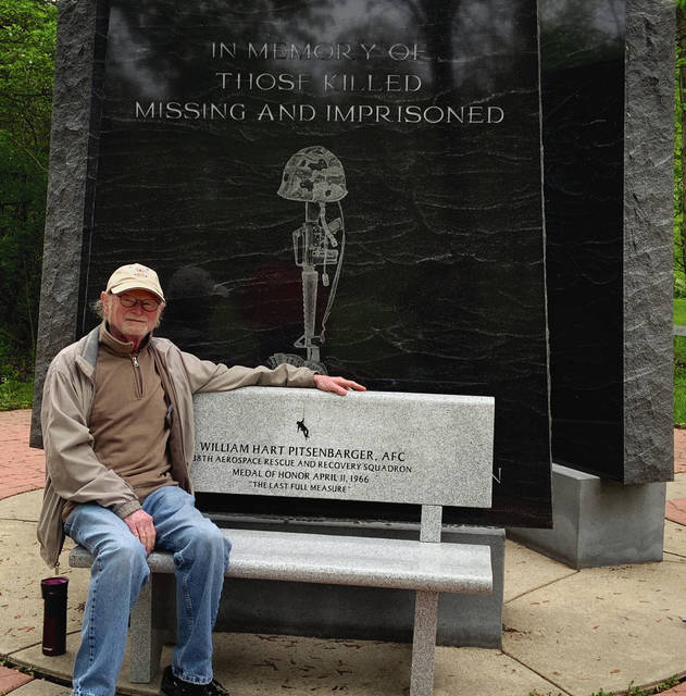 Bruce Lehman, a facilitator at the Veterans National Memorial Shrine and Museum in Fort Wayne, Ind., pose with the bench that Lionsgate donated in honor of Piqua native Airman 1st Class William H. Pitsenbarger, an Air Force pararescue specialist who died during the Vietnam War.
