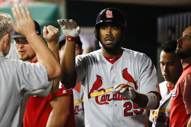 St. Louis Cardinals' Dexter Fowler celebrates in the dugout after hitting the game-tying solo home run off of Cincinnati Reds relief pitcher Kevin Shackelford in the eighth inning of a baseball game, Tuesday, Sept. 19, 2017, in Cincinnati. The Cardinals won 8-7 in 10 innings. (AP Photo/John Minchillo)
