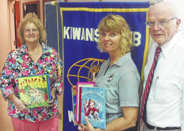 """As part of an ongoing literacy program, """"Readers Become Leaders,"""" the Wilmington Kiwanis Club donated children's books to the Clinton County Homeless Shelter. From left are Kiwanians Ann Reno, Kim Hiatt and Mack Fife."""