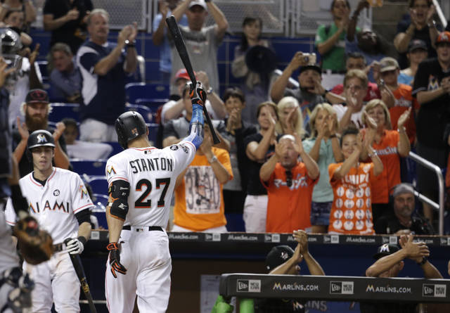 Miami Marlins' Giancarlo Stanton (27) raises his bat after he struck out swinging for his last at bat during the ninth inning of a baseball game against the Atlanta Braves, Sunday, Oct. 1, 2017, in Miami. The Braves won 8-5. Stanton finished the season with 59 home runs. (AP Photo/Lynne Sladky)