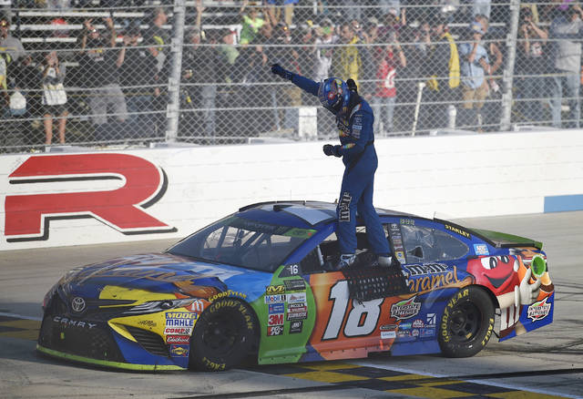 Kyle Busch celebrates atop his car after he won the NASCAR Cup Series auto race, Sunday, Oct. 1, 2017, at Dover International Speedway in Dover, Del. (AP Photo/Nick Wass)