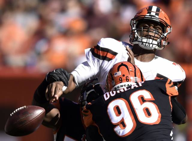 Cleveland Browns quarterback DeShone Kizer, top, loses control of the ball under pressure from Cincinnati Bengals defensive end Carlos Dunlap (96) in the second half of an NFL football game, Sunday, Oct. 1, 2017, in Cleveland. (AP Photo/David Richard)