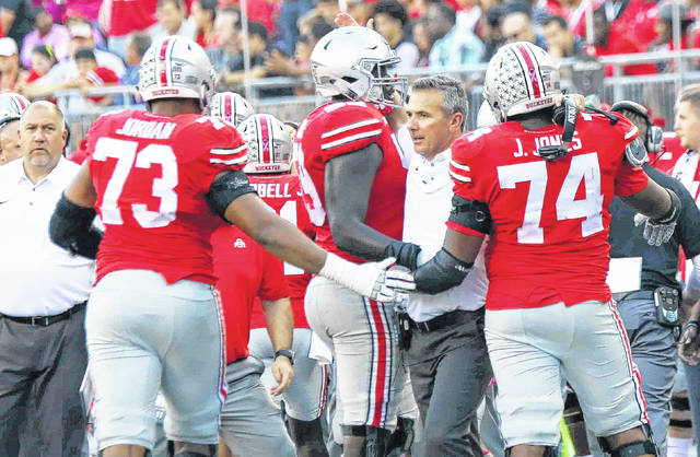 Former Wilmington College football coach Greg Studrawa (left) looks on as Ohio State head coach Urban Meyer congratulates a trio of offensive linemen during Saturday's win over Maryland. Studrawa is the offensive line coach at Ohio State. He was the offensive coordinator at Wilmington College from 1991 to 1996.