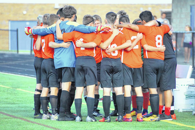 The Wilmington High School boys soccer team, shown here huddling prior to the first game of the year against Madeira, will play Tippecanoe 7 p.m. Friday in a Division II Southwest District championship match at Waynesville High School.