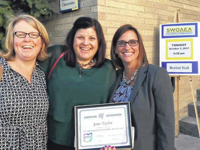 Wilmington Middle School art teacher Jane Taylor, middle, is accompanied by WCS Superintendent Mindy McCarty-Stewart, right, and Denver Elementary Principal Karen Long, left, when she accepted the Southwestern Ohio Art Education Association's Outstanding Art Teacher of the Year certificate.