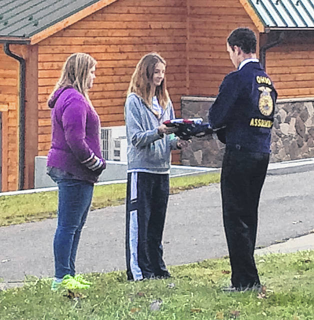 Eighth grade FFA members Madison Pembleton and Emma Winemiller assist state FFA officers in raising Old Glory before breakfast at Greenhand Camp.
