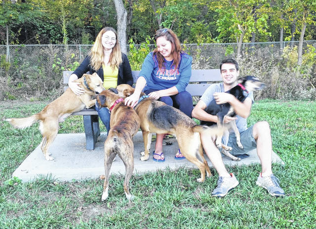 Shown at the dog park are, from left, Alisha Arbino, Courtney Kremer and and Tom Somrack, along with their furry friends.