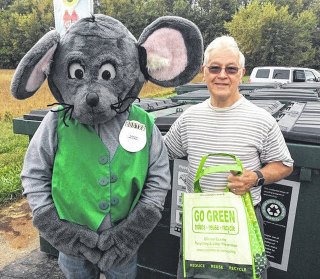 "Thomas Hovan was the first culprit in the annual Get Caught Recycling Campaign. Buster the Mouse, from the Clinton County Solid Waste District, caught Thomas ""green-handed"" putting the proper recyclables into the community drop-off recycling container located at Streber's Market in New Vienna. This year's Get Caught Recycling theme is Rest & Relaxation. For his efforts in practicing the 3 R's, Thomas received several recycled content prizes, including a hammock, shopping bag, and other such prizes. Don't miss out on this chance to win great prizes by simply recycling household items such as bottles, jars, and newspapers. For a list of the local recycling drop-off locations and acceptable materials, visit the SWMD's website at www.co.clinton.oh.us/recycling. There are still three weeks left in the campaign, so be on the lookout … you could be the next person caught green-handed"