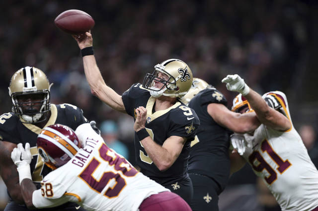 New Orleans Saints quarterback Drew Brees (9) passes under pressure from Washington Redskins linebacker Junior Galette (58) and outside linebacker Ryan Kerrigan (91) in the first half of an NFL football game in New Orleans, Sunday, Nov. 19, 2017. (AP Photo/Rusty Costanza)