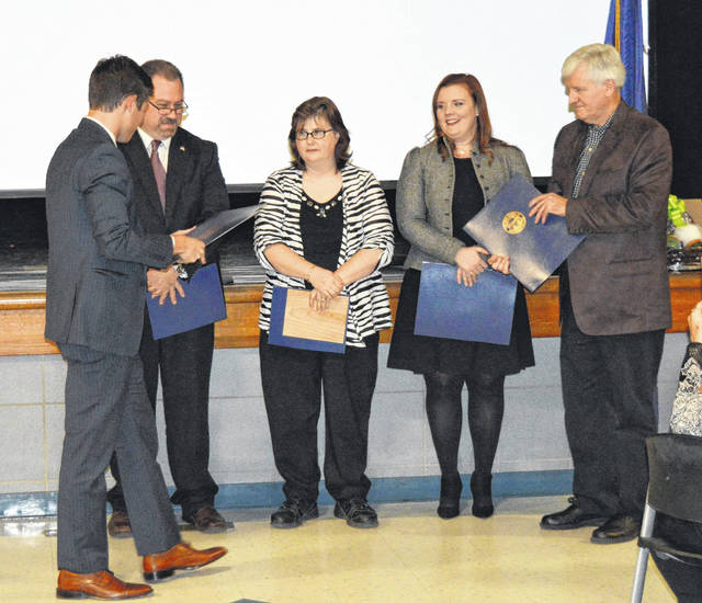 A representative from the office of Ohio House Speaker Cliff Rosenberger, Jack Brubaker, recognized Blanchester Area Chamber of Commerce honorees — from left, Paul Casteel, Lisa Beach, Leigh Jones and Parker Beebe — at Tuesday night's 62nd annual meeting and dinner held at the high school.