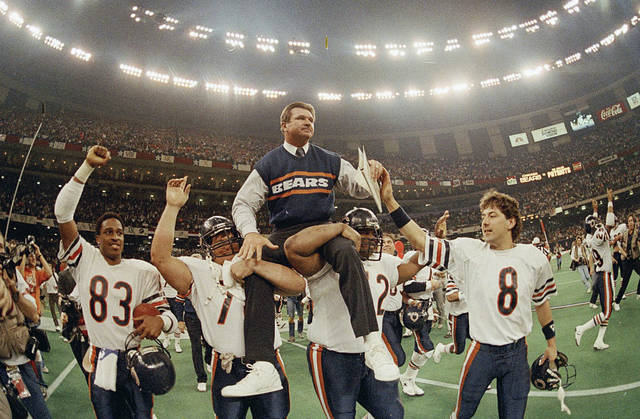 """FILE- In this Jan. 26, 1986, file photo, Chicago Bears head coach Mike Ditka is carried off the field by Steve McMichael, left, and William Perry after the Bears defeated the New England Patriots 46-10 in  Super Bowl XX in New Orleans. Argue all you want about which is the best team in NFL annals. The Pro Football Hall of Fame has opted for the 1985 Chicago Bears. The Canton shrine will premiere """"85: THE GREATEST TEAM IN FOOTBALL HISTORY"""" on Jan. 3. It will then hit theaters nationwide on Jan. 29.  (AP Photo/Phil Sandlin, File)"""