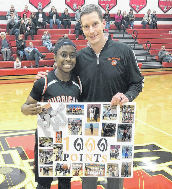 Mya Jackson became the fifth member of the Wilmington High School girls basketball program 1,000 career points club Thursday night at New Richmond. Jackson is shown with WHS head coach Zach Williams following the milestone points which came on a layup in the first period.