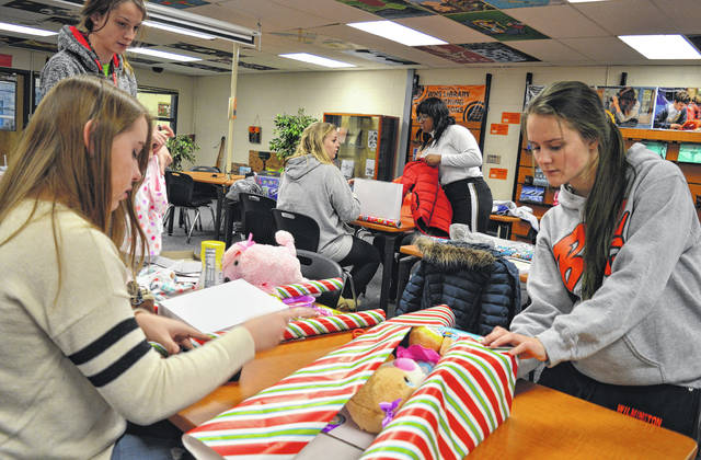 Wrapping gifts are Interact Club WHS seniors Abigail Tackett, Carrissa Miller and Samantha Burns.