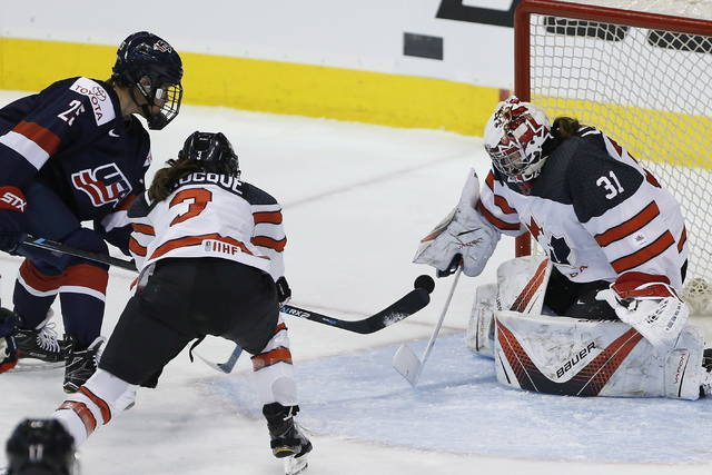 FILE - In this Dec. 5, 2017, file photo, Canada goalie Genevieve Lacasse (31) saves a shot by United States' Alex Carpenter (25) as Canada's Jocelyne Larocque (3) defends during the first period of a hockey game in Winnipeg, Manitoba. Canada goaltender Shannon Szabados is going for her third gold and Lacasse won her first in 2014. (John Woods/The Canadian Press via AP, File)