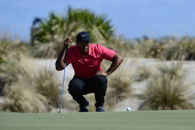 FILE - In this Dec. 3, 2017, file photo, Tiger Woods lines up a putt on second hole during the final round of the Hero World Challenge golf tournament at Albany Golf Club in Nassau, Bahamas. Woods makes his return to the PGA Tour this week at the Farmers Insurance Open. (AP Photo/Dante Carrer, File)
