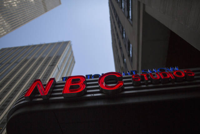 FILE - This Wednesday, May 10, 2017, file photo, shows the NBC logo at their television studios at Rockefeller Center in New York. Comcast's NBC is airing both the Super Bowl and the Olympics in February 2018, a double-whammy sports extravaganza that the company expects to rake in $1.4 billion in ad sales, helping it justify the hefty costs it's paying for these events. (AP Photo/Mary Altaffer, File)
