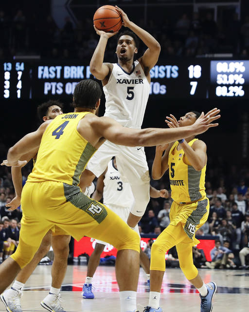 Xavier's Trevon Bluiett (5) shoots and reaches his 2000th career points total in the second half of an NCAA college basketball game against Marquette, Wednesday, Jan. 24, 2018, in Cincinnati. Xavier won 89-70. (AP Photo/John Minchillo)