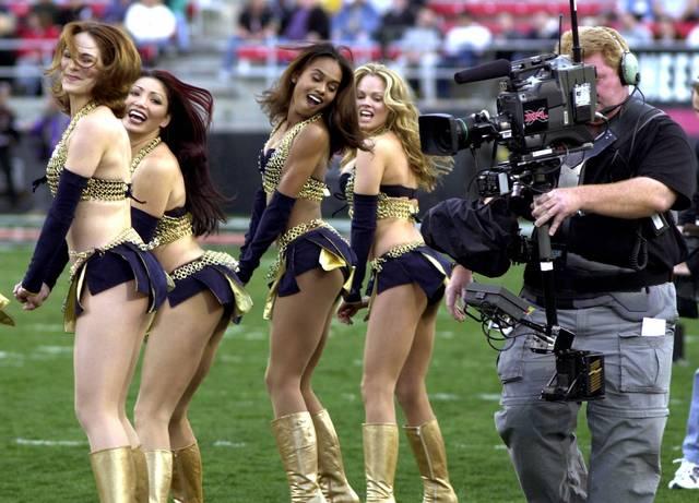 FILE - In this Feb. 17, 2001, file photo,a  television cameraman photographs the Los Angeles Xtreme cheerleaders before the start of an XFL football game between the Xtreme and the Las Vegas Outlaws in Las Vegas. The XFL is set for a surprising second life, WWE leader Vince McMahon announced Thursday, Jan. 25, 2018. McMahon said the XFL would return in 2020 but offered few other details about the late winter/early spring football league. (AP Photo/Jeff Klein, File)